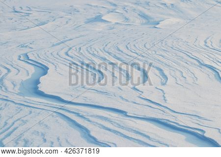 Snowy Background, Snow-covered Surface Of The Earth After A Blizzard In The Morning In The Sunlight