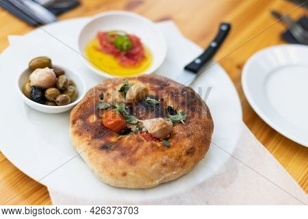 Italian Focaccia With Cherry Tomatoes, Thassos Olives, Oregano, Olive Oil And Sea Salt. Served With