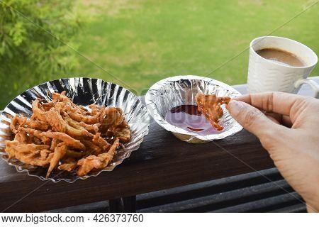 Female Eating Tasty Onion Pakoda Or Pyaz Ke Pakode, Bhajiya. Indian Pakistani Tea-time Snacks Onion