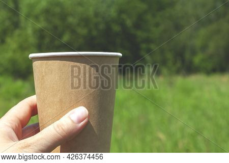 Hand Holding A Disposable Brown Cardboard Cup With A Drink On The Left Close-up On A Natural Backgro