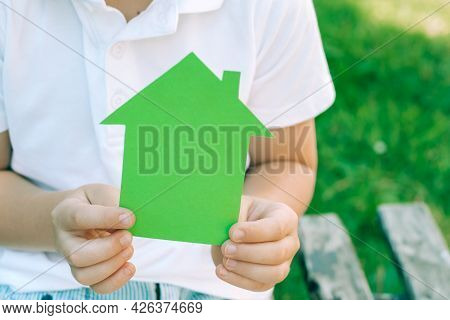 Green Paper House In The Hands Of A Child. Concept Of Ecological Houses. Outdoors