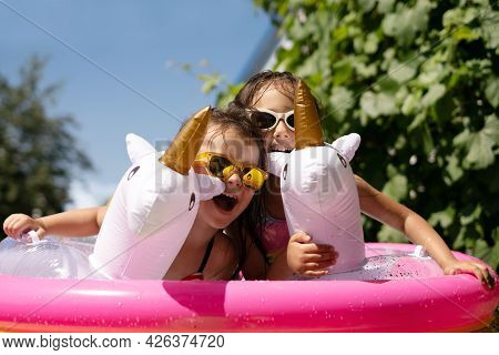 On A Hot Summer Day, Two Children Are Frolicking At Home In An Inflatable Pool With Lifebuoys In The