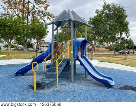 Slide, Swing On Modern Playground. Children Playground Activities In Public Park. Urban Neighborhood