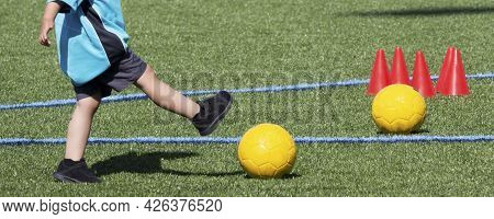 Preschool Boy Kicking A Yellow Soccer Ball During Practice With Another Ball And Orange Cones On The