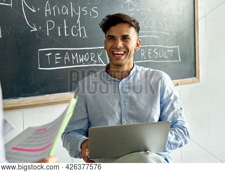 Young Happy Indian Latin Man Student With Laptop Laughing During College Seminar Class. Smiling Llat