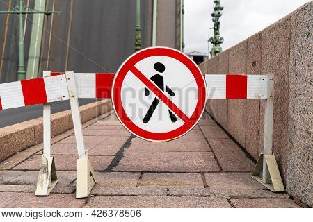 Barrier Blocking Sidewalk And Sign With Picture Of Crossed-out Man Prohibiting The Passage Of Pedest
