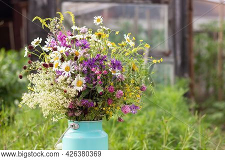 Bouquet Of Bright Wild Flowers In Tin Can Vase On Table Outdoors, Rural Scene. Template For Postcard