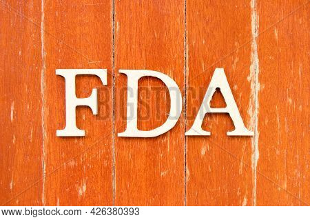 Alphabet Letter In Word Fda (abbreviation Of Food And Drug Administration) On Old Red Color Wood Pla