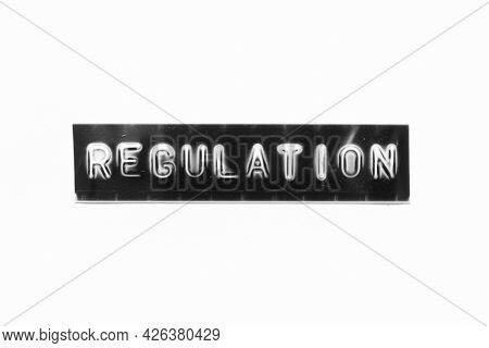 Embossed Letter With Word Regulation In Black Banner On White Paper Background