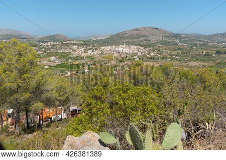 Spanish Landscape With Small Historic Town Of Parcent In Distance From Coll De Rates Mountains, Spai