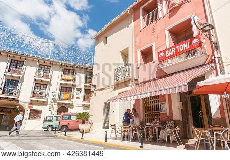 Parcent Spain - August 23 2016; Spanish Village Scene Man Crosses Street While Women Enjoy Morning D