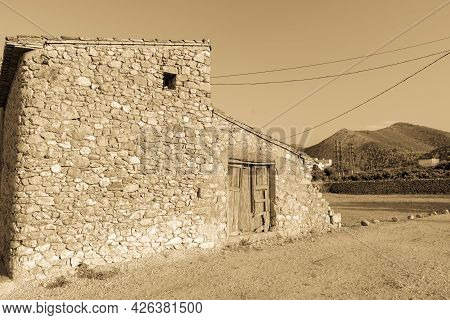 Old Stone Building With Dilapidated Wooden Doors In Rural Spain In Sepia Monotone Image.