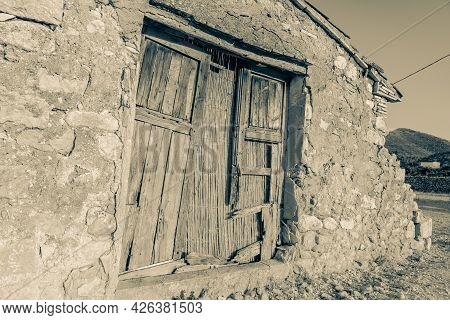 Dilapidated Wooden Doors In Old Stone Rural Building In Monochrome Effect