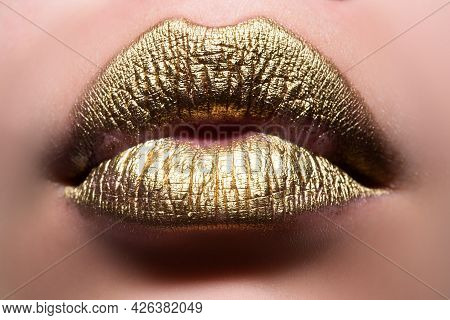 Gold Lips. Woman Wouth Close Up With Golden Color Lipstick On Lip. Glitter Glossy Lips Biting.