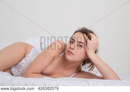 Young Woman Model Lying On Bed At Bedroom. A Woman Lying In Bed And Smiling.