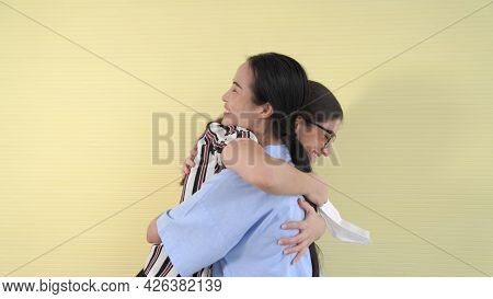 Happy Friends Take Off Face Mask And Hug Each Other Closely Together Showing Concept Of The End Of Q