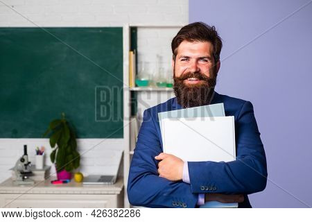 Smiling Teacher Professor Standing In Front Of Blackboard Teaching Student In Classroom. Handsome Sc