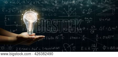 Businessman Hand Holding Human Brain Glowing Inside Of Light Bulb On Abstract Dark Sketches Backgrou