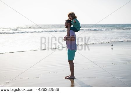 Dad And Child Walking Together On Summer Beach. Little Boy Kid With Daddy Carrying Him On Shoulders.