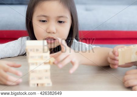 Asian Little Girl Playing Game Build Wood Toy With Friends On Table At Home, Children Concentration