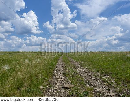 Dirt Road In The Steppe Stretching Beyond The Horizon. Spring Landscape With Clouds, Blooming Steppe