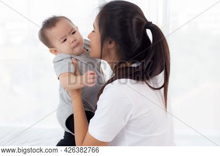 Young Asian Mother Holding Little Baby Girl Together In The Bedroom At Home, Mom Carry Child And Car