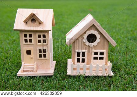 Neighbors House Concept. Toy Model House In He Middle Of Large Grass Meadow Field. Mortgage Payment,