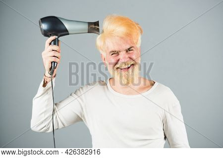 Stylish Man With Hair Dryer And Funny Expressions In The Barbershop. Blonde Bearded Man Hair Dry.