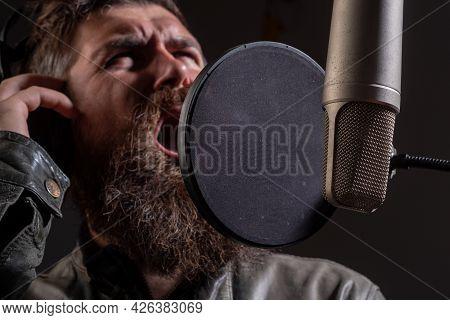 Karaoke Singer. Expressive Face Closeup. Man Singing With Music Microphone.