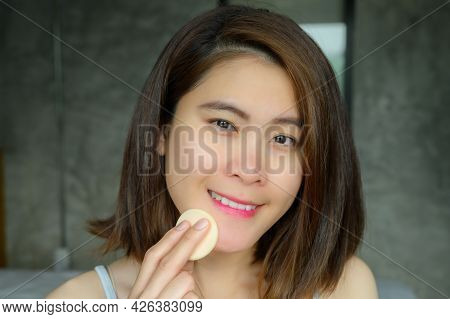 Portrait Of Young Attractive Asian Woman Applying Foundation Powder Puff On Her Face To Cover Flaws
