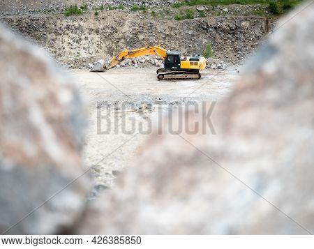 Heavy Excavator Working On Earthmoving At Open Granite Mine. Crawler Machine Works Excavating In  Qu