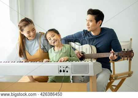 Happy Little Asian Family Daughter Playing Piano With Mother And Father Play Guitar At Home, Mother