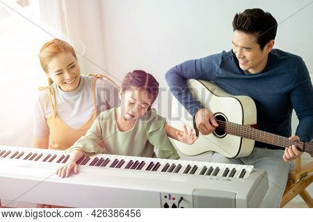 Happy Little Asian Family Daughter Playing Piano With Mother And Father Play Guitar At Home, They Pl