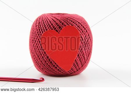 A Crimson Ball Of Thread With A Red Heart For Crocheting And Crocheting On A White Background. The C