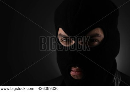 Man Wearing Knitted Balaclava On Black Background, Closeup. Space For Text