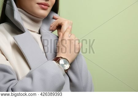 Woman With Luxury Wristwatch On Green Background, Closeup. Space For Text