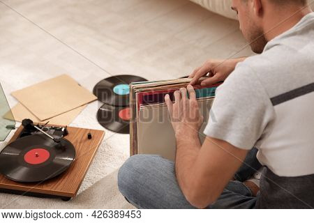 Man With Collection Of Vinyl Records Near Turntable At Home