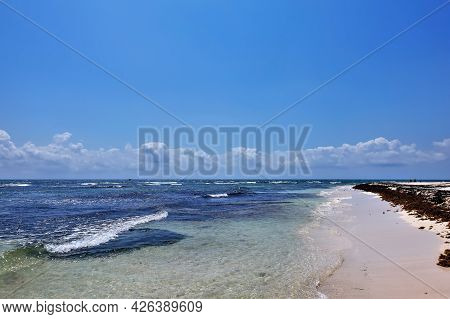 Beach On The Caribbean Coast. Transparent Turquoise Water With The Foam Of The Waves. Algae On The S