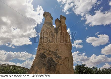 The Amazing Landscape Of Cappadocia. A High Cliff With Steep Slopes Against A Blue Sky. A Three-head
