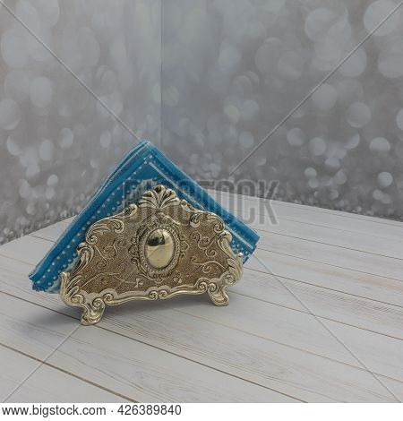 A Metallic Gold Napkin Holder With A Blue Paper Napkin Stands On A White Board Table. Decorated With