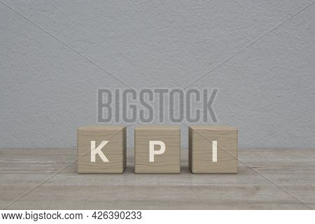 Kpi Letter On Block Cubes On Wooden Table Over White Wall Background, Key Performance Indicator Busi