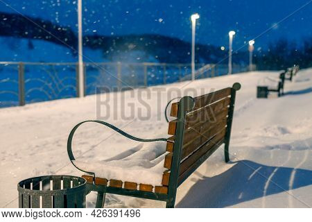 Empty Benches In A Winter Evening During A Snowfall In The Park. Rear View Of Bench And Lantern Ligh