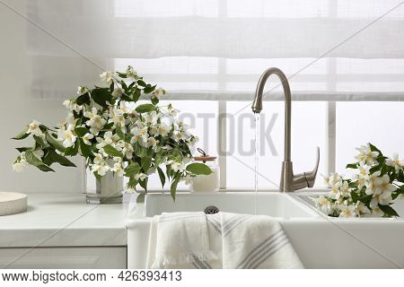 Bouquet Of Beautiful Jasmine Flowers In Vase On Countertop Near Kitchen Sink