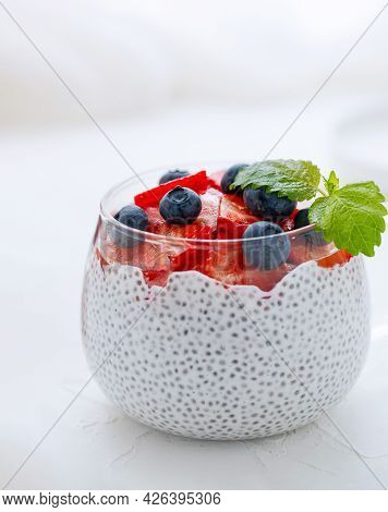 Healthy Chia Pudding With Coconut Milk, Strawberries, Chia Seeds, Blueberries In A Glass. Concept Of