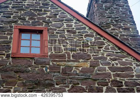 Closeup Of Architectural Features In Stone Colonial Construction Home Exterior Facade. Roofline, Red