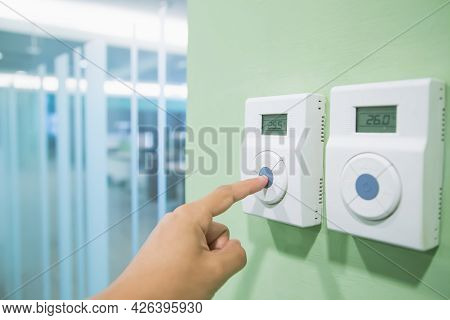 Remote Air Conditioner, Hand Is Adjusting Temperature At The Thermostat Remote Control Switch Of The