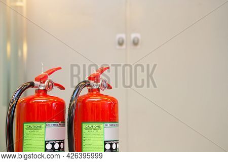 Fire Extinguisher, Close-up Red Fire Extinguishers Tank With Door Exit Or Fire Escape In The Buildin