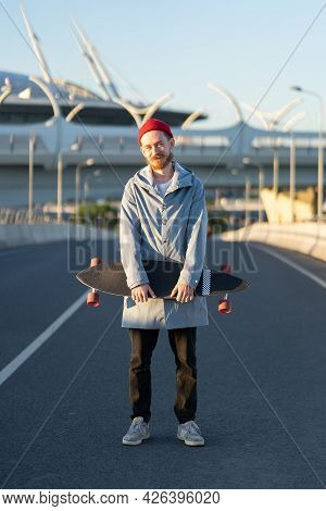 Young Hipster Man In Red Hat Holding Longboard In City Street Over Modern Buildings Background. Tren