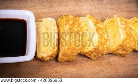 Japanese Omelet Tamago Yaki In The Form Of Rolls On A Wooden Board With A Chunk Of Soy Sauce