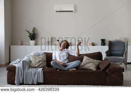 Peaceful African American Woman Using Air Conditioner Remote Controller